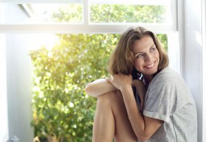 Mature Model Sitting on Window Sill Smiling