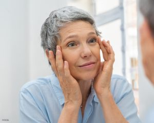 Older Women With Short Grey Hair Looking in the Mirror Examining her Eye Wrinkles