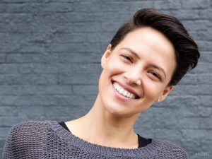 Woman with Black Pixie Cut Hair Smiling and Titling Head to the Side